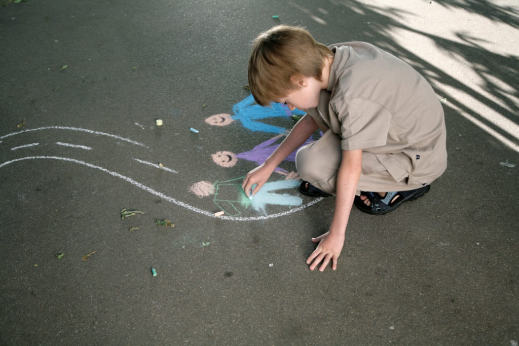 Gutt tegner mennesker med gategritt